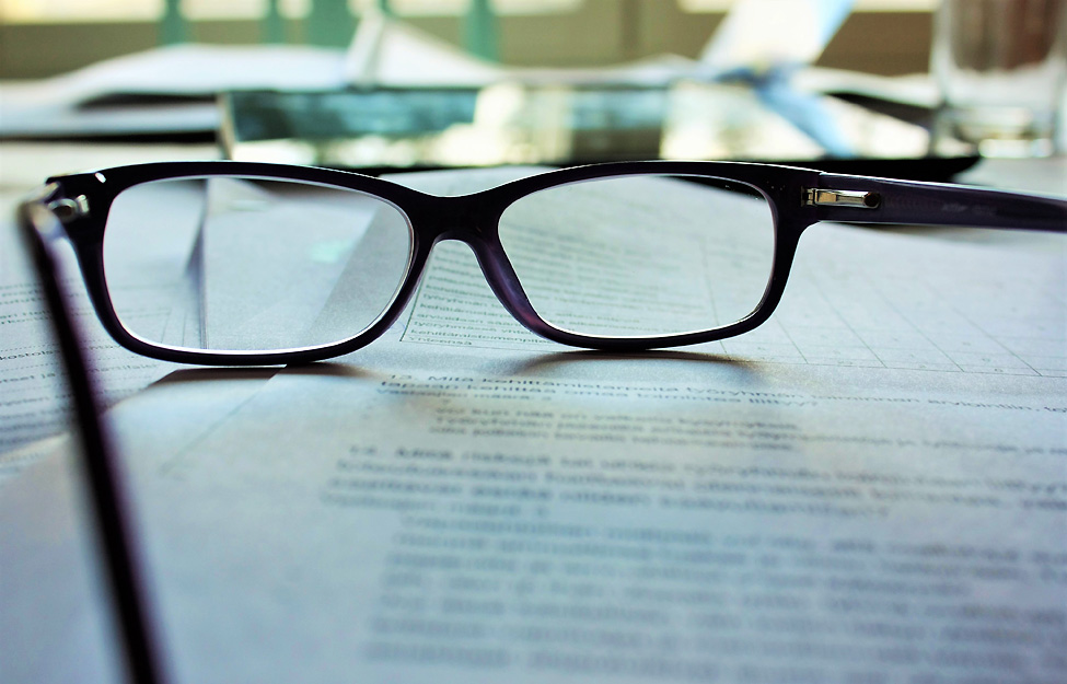 Photo of eye glasses sitting on top of office documents